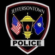 Jeffersontown Police department seal, with oil lamp in center flanked by U.S. flag on left and Kentucky flag on right
