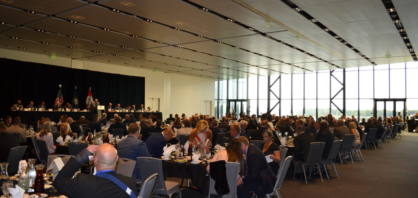Awards ceremony for Kentucky Association of Police Chiefs conference at the Owensboro Convention Center in Owensboro, Ky. To the left in the background is a raised stage with several people behind a table and someone at the lectern. Many tables filled with people surround several rows back and wide windows of the convention center open to the far right in the distance.