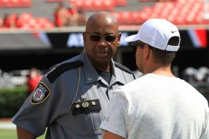 Medium closeup of City of Murray Chief of Police Jeff Lilies, standing on the field in a stadium with a man standing in front of him.