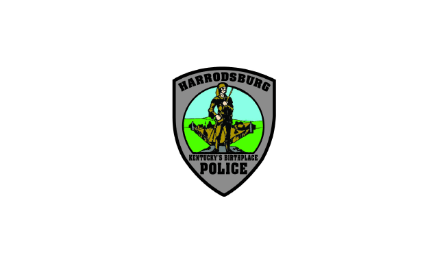 """Harrodsburg Police Logo in form of shield. """"Kentucky's Birthplace"""" is at bottom below an illustration of an early pioneer with a fur hat, leather clothes, and holding a musket in front of a fort."""