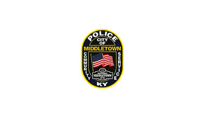 """City of Middletown Police, design is an oval with an American flag waving at the center with """"community"""" and """"service"""" vertically on the left and right respectively. At the bottom a banner reads """"Historic Middletown"""" with KY at the base of the oval beneath this banner."""