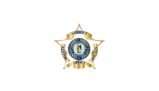 """Kenton County Sheriff's Office badge. Four banners around a 5-pointed star read """"Kenton"""" on left, """"County"""" on the right, """"Sheriff"""" across the top, and """"Office"""" across the bottom. In the center here is a circle, around the outside ring the words read """"Kenton County Sheriff's Office."""" In the second inside ring it reads """"Commonwealth of Kentucky."""" At the very center is an interpretation of the seal from the Kentucky state flag with a pioneer and a statesman shaking hands, and below their feet a banner reads """"United We Stand, Divided We Fall"""""""